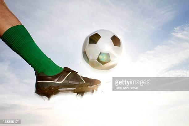 Man kicks a football into the sky shooting a goal