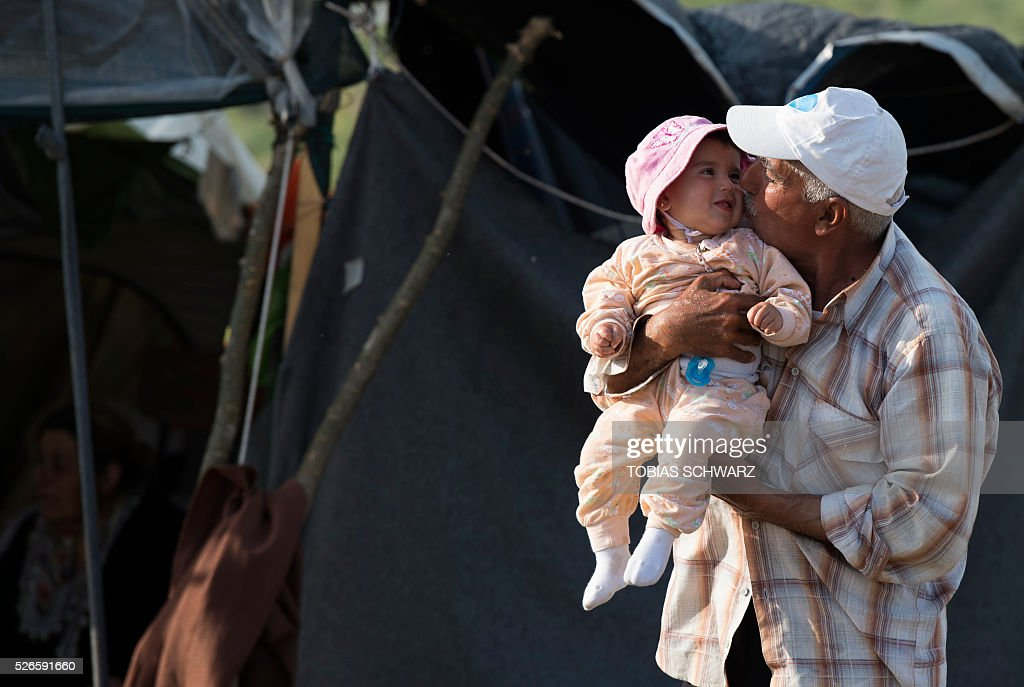 A man kisses a child at a makeshift camp for migrants and refugees near the village of Idomeni not far from the Greek-Macedonian border on April 30, 2016. Some 54,000 people, many of them fleeing the war in Syria, have been stranded on Greek territory since the closure of the migrant route through the Balkans in February. / AFP / TOBIAS