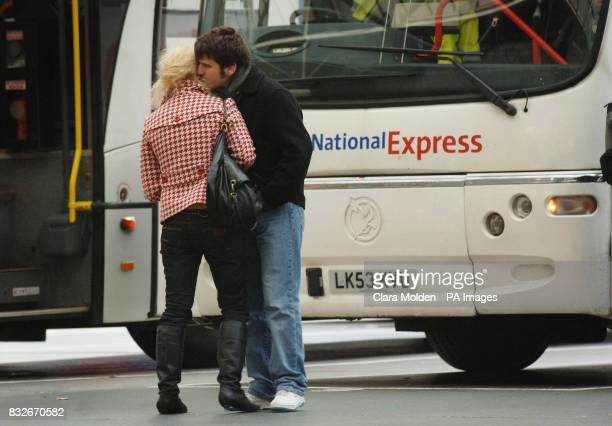 A man kisses a woman goobye before she boards a National Express coach heading for Stanstead Airport in Victoria coach station London