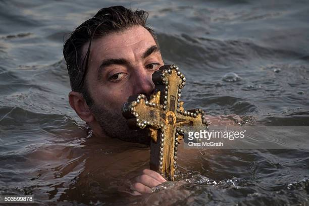 A man kisses a wooden cross after retrieving it from the Bosphorus river during the blessing of the water ceremony as part of celebrations of the...
