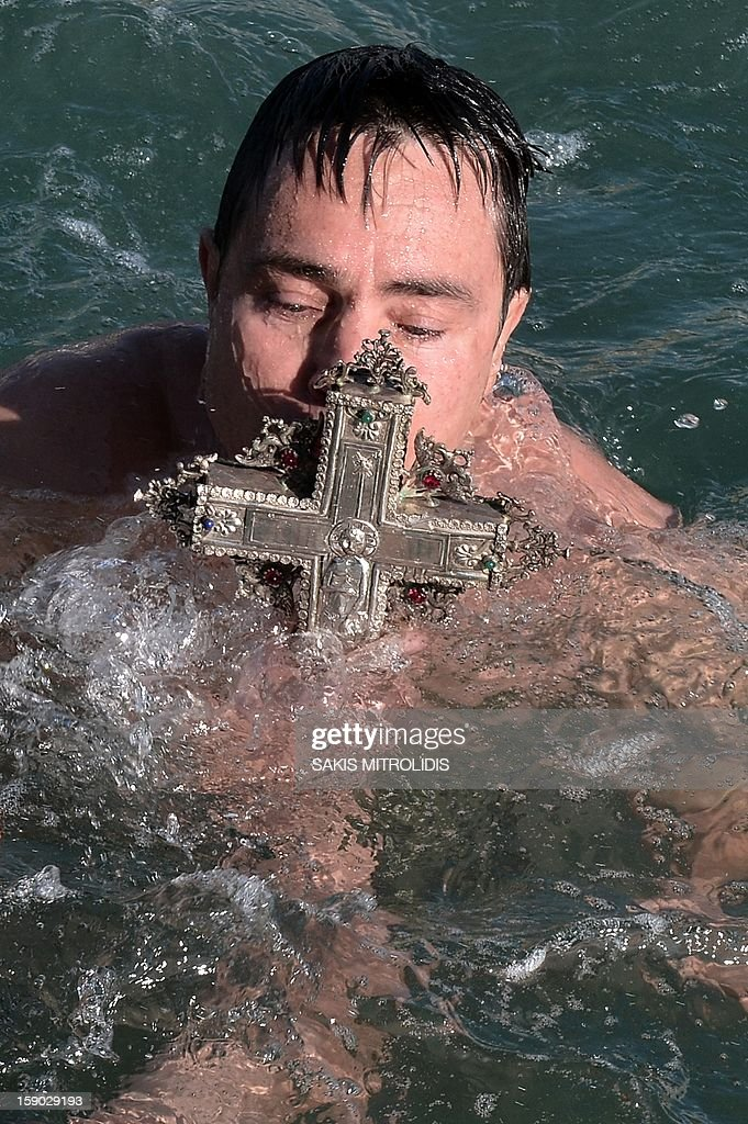 A man kisses a wooden cross after retrieving it from the sea during an Epiphany ceremony in Greece's northern port of Thessaloniki on January 6, 2013. Similar ceremonies to mark Epiphany Day are held across the country on river banks, seafronts and lakes. AFP PHOTO /Sakis Mitrolidis
