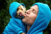 Man Kisses Best Friend Dog Matching Blue Hoodies at Park