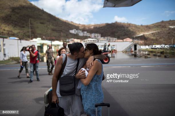 TOPSHOT A man kisses his wife holding their baby as they board a plane at GrandCase Esperance airport to leave SaintMartin on September 10 2017 on...