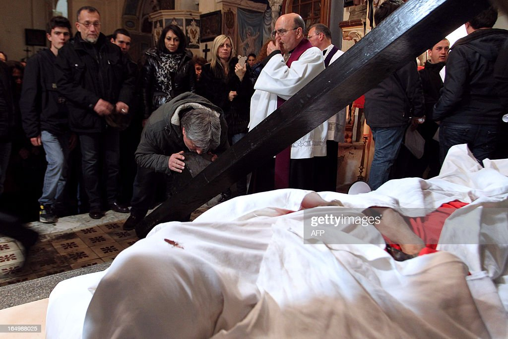 A man kisses the cross of the 'catenacciu,' a hooded and chained penitent who reenacted the crucifixion of Jesus Christ as part of a Good Friday in the village of Bisinchi, on the French mediterranean Island of Corsica, on March 30, 2013. AFP PHOTO / PASCAL POCHARD-CASABIANCA