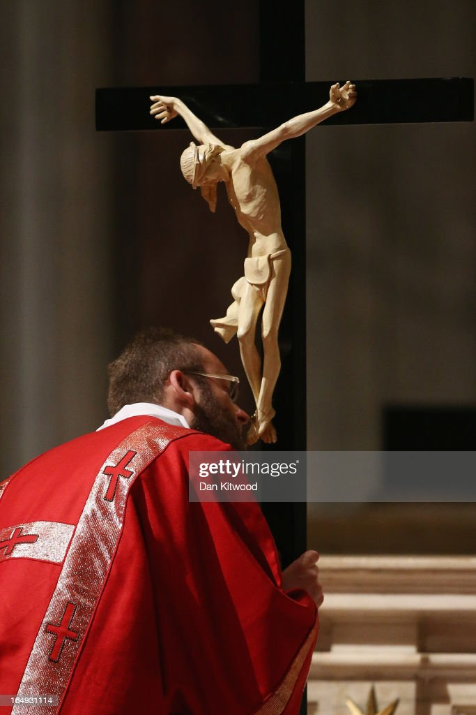 A man kisses the feet of Jesus Christ on the cross as others wait in line to kneel before the crucifix during a Papal Mass with the Celebration of the Lord's Passion lead by Pope Francis inside St Peter's Basilica on March 29, 2013 in Vatican City, Vatican. Pope Francis is taking part in his first holy week as pontiff and will later today preside over the Way Of the Cross procession at the Colosseum in Rome.