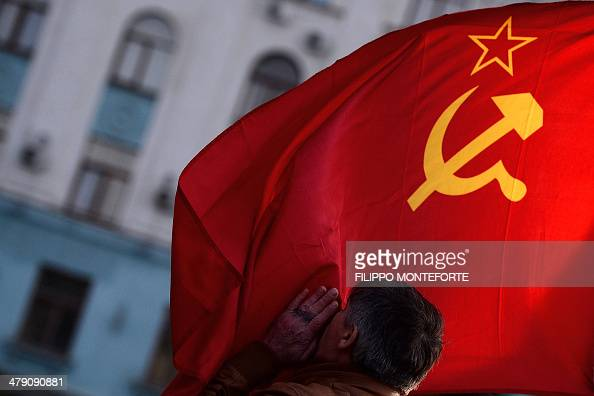 A man kisses the Soviet Union flag in Simferopol's Lenin Square on March 16 2014 Polls opened today in a referendum on the peninsula of Crimea in...