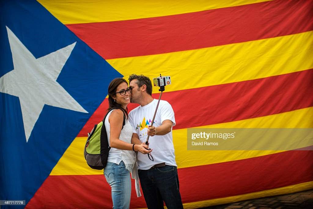 A man kisses to his girlfriend as they take a selfie in front of a Catalan ProIndependence flag before a ProIndependence demonstration celebrating...
