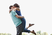 Man kissing and lifting wife outdoors
