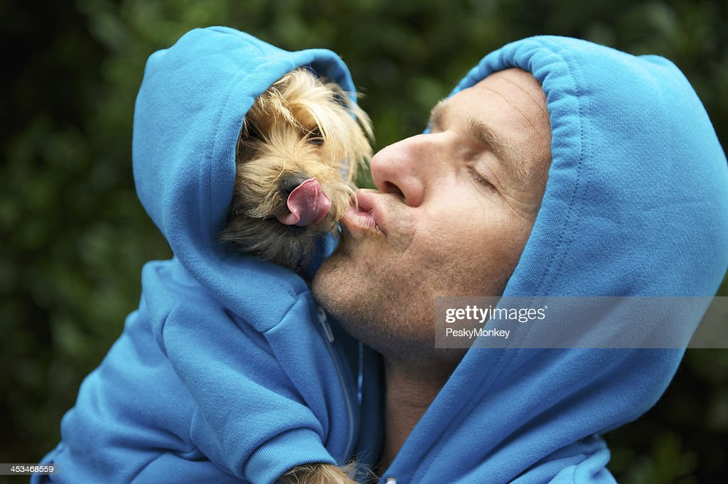 Man kisses his best friend dog in matching blue hoodies in bright green park background outdoors