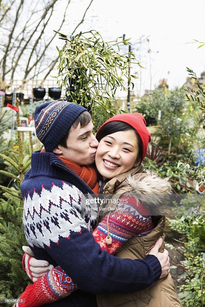 Man kissing girlfriend while holding mistletoe.. : Stock Photo