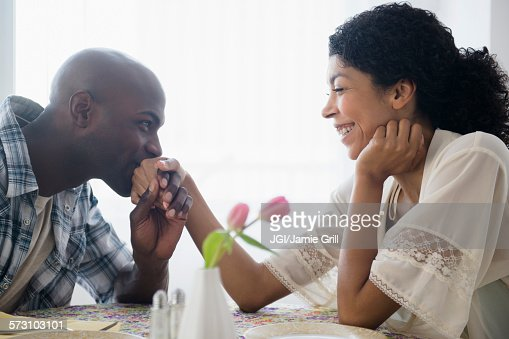 Man kissing hand of girlfriend at restaurant table