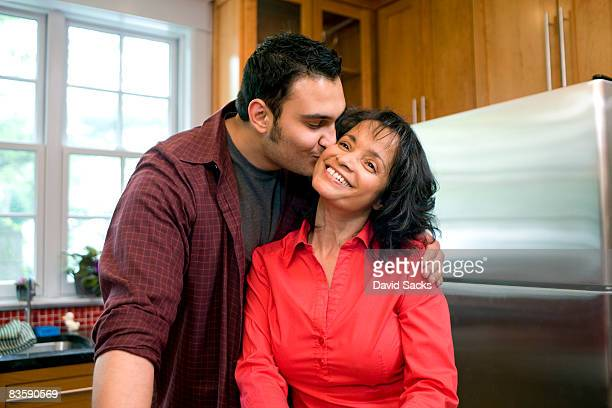 Man kissing his mother on cheek in kitchen