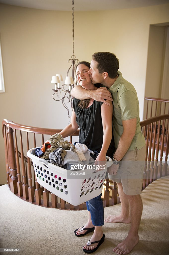 man kissing his wife with load of laundry : Stock Photo