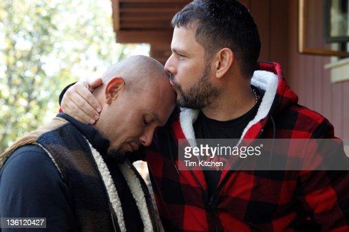 Man kissing man on forehead, profile