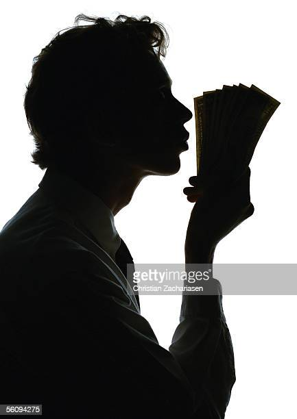Man kissing money, silhouette.