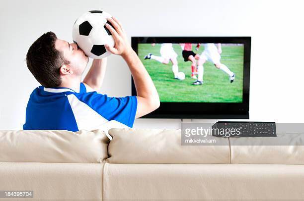 Man kissing soccer ball in front of a tv