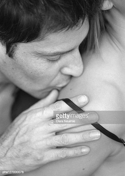 Man kissing woman, close-up, b&w