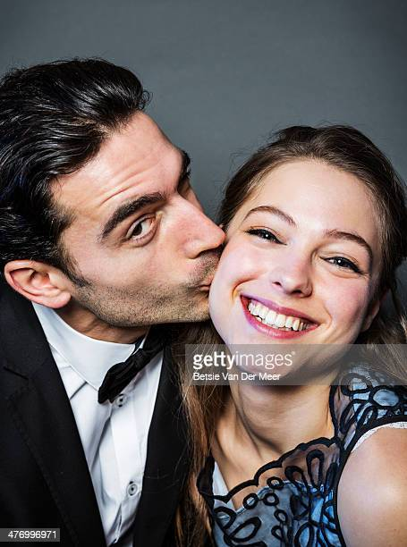 Man kissing woman for photobooth photo.