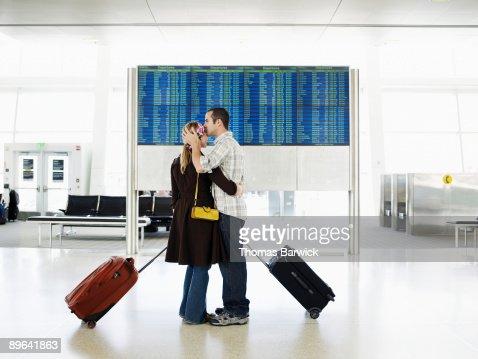 Man kissing woman in airport near departure board