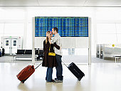 Man kissing woman in airport near departure board