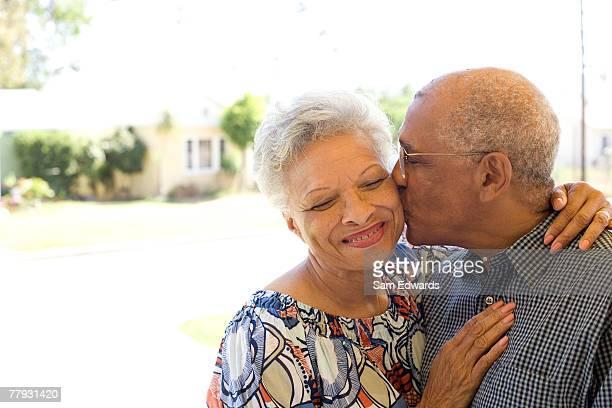 Mann Küssen Frau auf Wange im Freien
