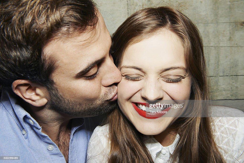 man kissing woman on cheek
