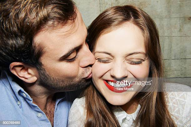 man kissing woman on cheek