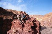 Man kissing woman on rock