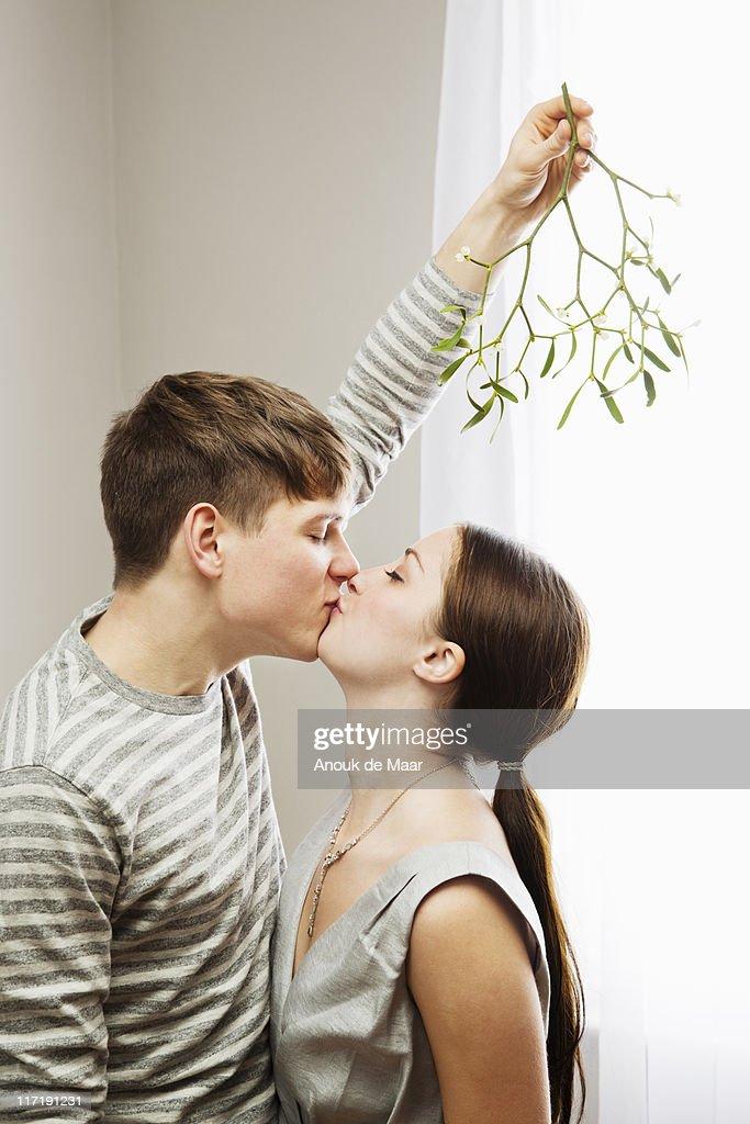 Man kissing woman while holding mistleto