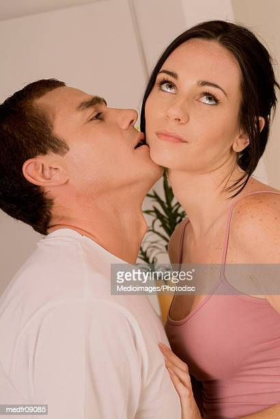 Man kissing woman who looks bored, close-up