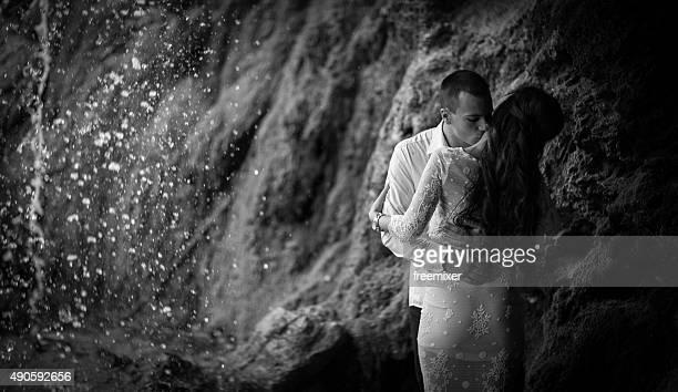 Man kissing woman`s cheek under waterfall