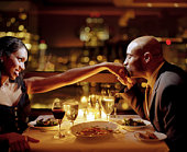 Man kissing woman's hand at restaurant table, side view