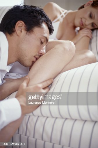 Man kissing woman's leg, close-up : Stock Photo