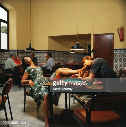 Man kissing woman's toes in bar : Stock Photo