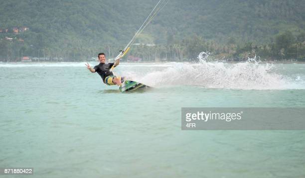 Man kite surfing on vacation, laughing towards the viewer