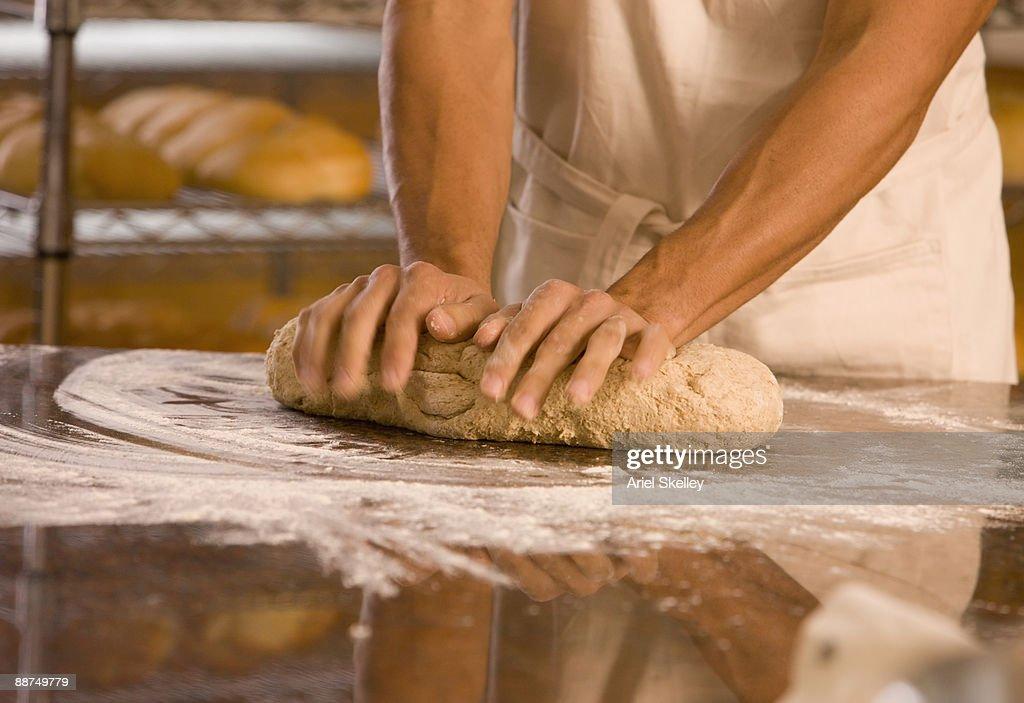 Man kneading dough at bakery : Stock Photo