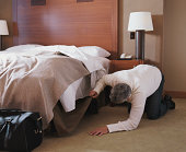 Man kneeling on floor in hotel room, looking under bed