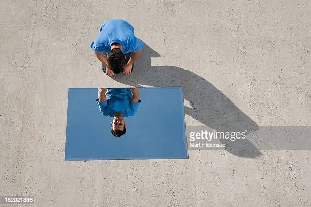 Man kneeling on ground with mirror and reflection