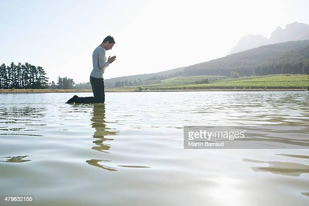 Mann kniend auf dem Wasser Beten