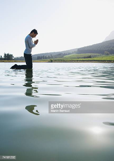 Man kneeling on water praying