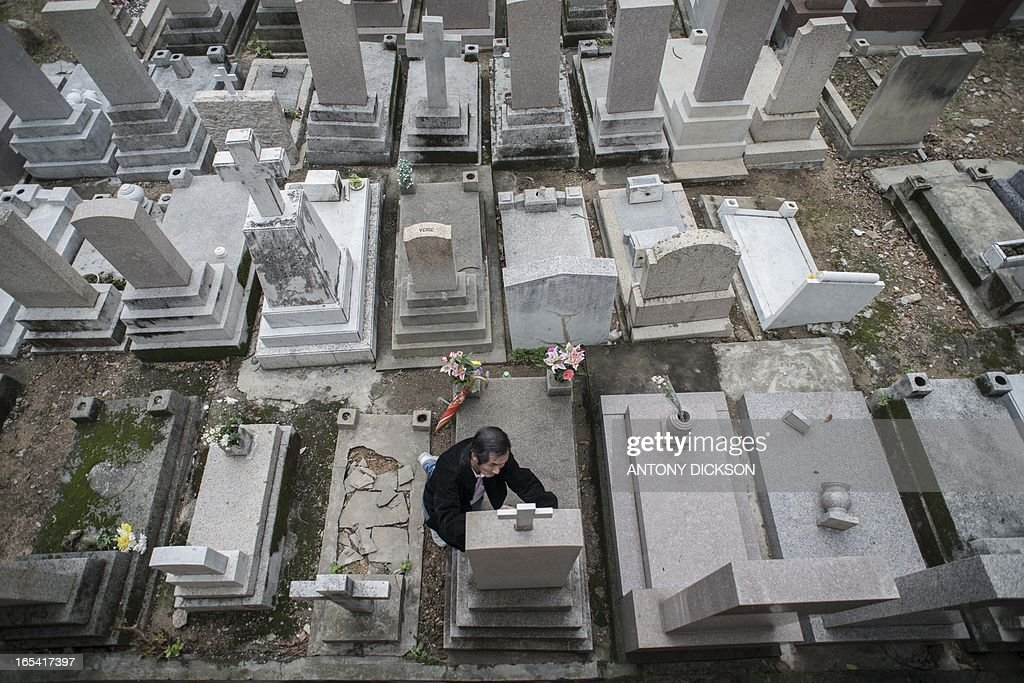 A man kneels as he retraces with a black pen the inscription on the tombstone of a loved one, at a Catholic cemetary during Ching Ming Festival, or grave-sweeping day in Hong Kong on April 4, 2013. Visiting the graves of ancestors during Ching Ming, this year marked on April 4, is an age-old Chinese tradition dating back 2000 years to the Han dynasty. AFP PHOTO / Antony DICKSON