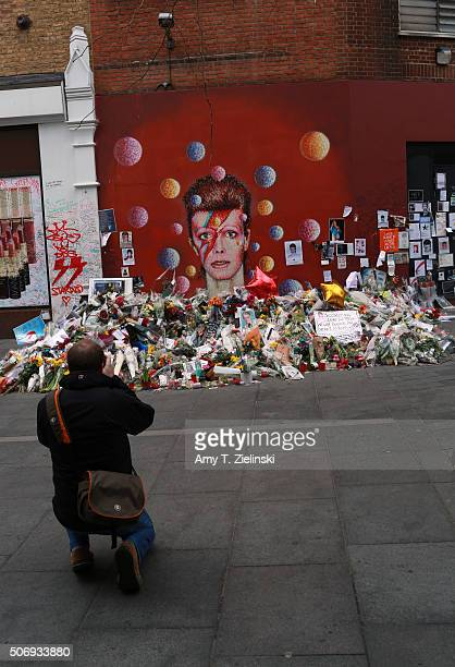 A man kneels down to photographer the flowers letters and other items left on a mound continue to grow two weeks after the death of Brixton born...