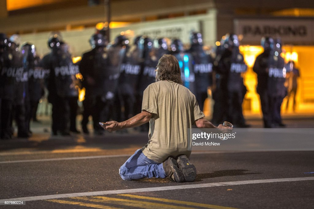 A man kneels in the street as police officers advance upon demonstrators after a rally by President Donald Trump at the Phoenix Convention Center on August 22, 2017 in Phoenix, Arizona. An earlier statement by the president that he was considering a pardon for Joe Arpaio, the former sheriff of Maricopa County who was convicted of criminal contempt of court for defying a court order in a case involving racial profiling, has angered Latinos and immigrant rights advocates.