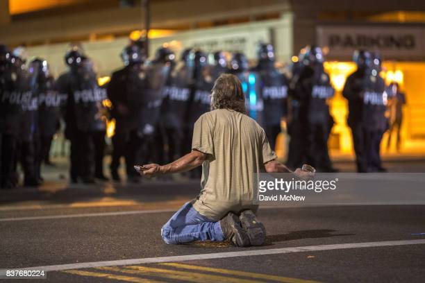 A man kneels in the street as police officers advance upon demonstrators after a rally by President Donald Trump at the Phoenix Convention Center on...