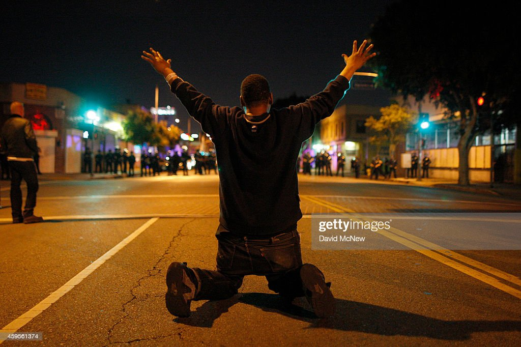 A man kneels in the street before a line of police officers about to charge at protesters reacting to the grand jury decision not to indict a white...