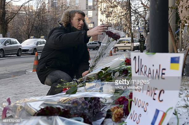 A man kneels to place flowers in front of the French embassy in Kiev where people have placed candles and flowers on January 8 in tribute to the...