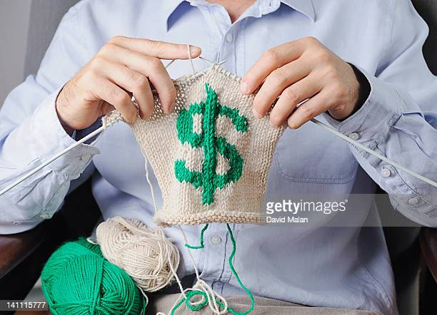 Man knitting a dollar sign.