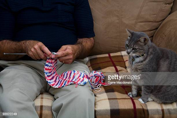 Man knitting a scarf with cat watching
