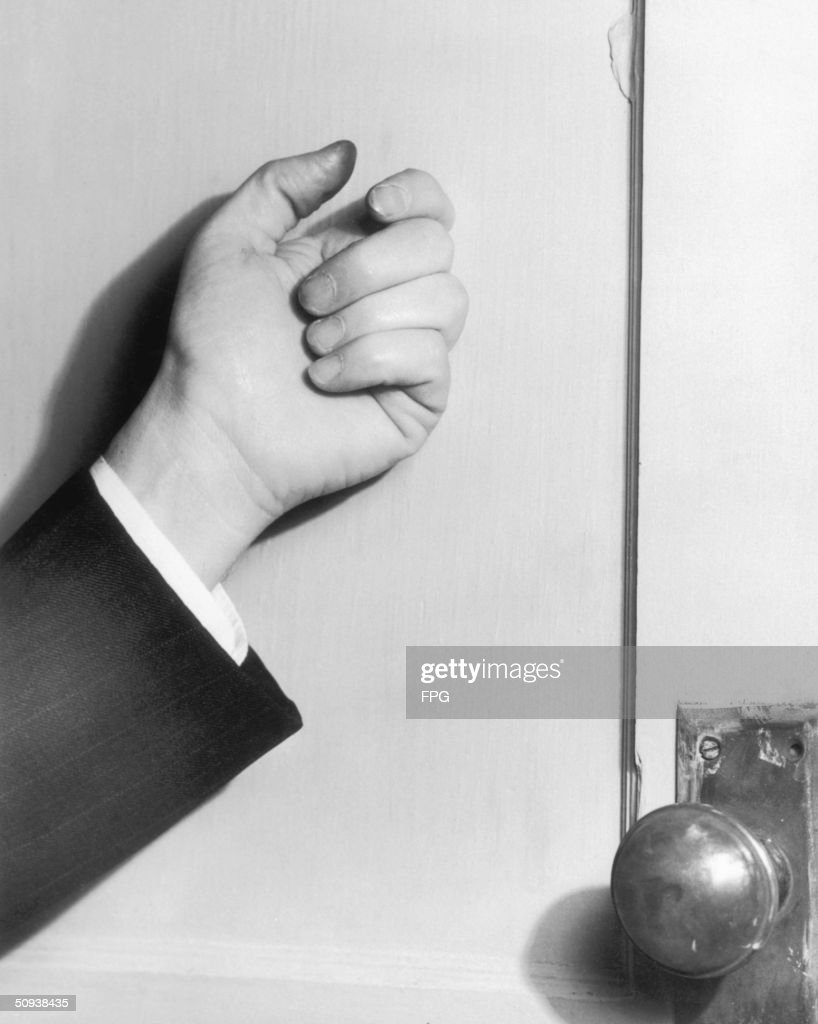 A man knocking on a door circa 1950