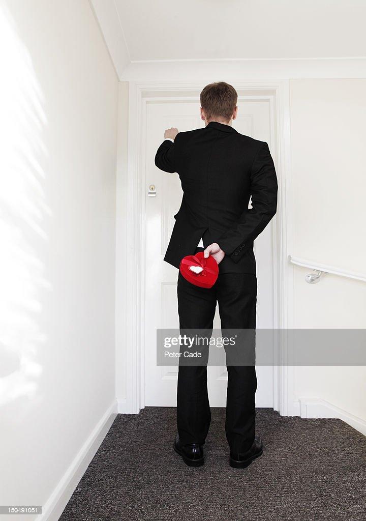 Man knocking on door holding heart shaped box